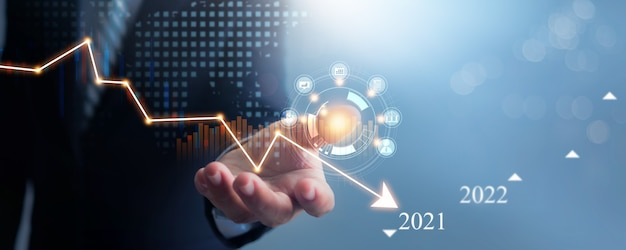 Hand van zakenman in pak houdt en ondersteunt economische neergang in 2021