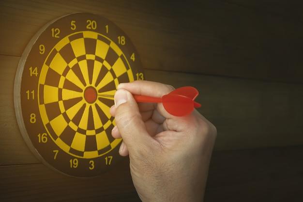 Hand van zakenman prikkende pijltje binnen aan dartboard, succes bedrijfsconcept