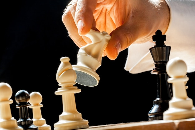 Hand van zakenman schaak spelen