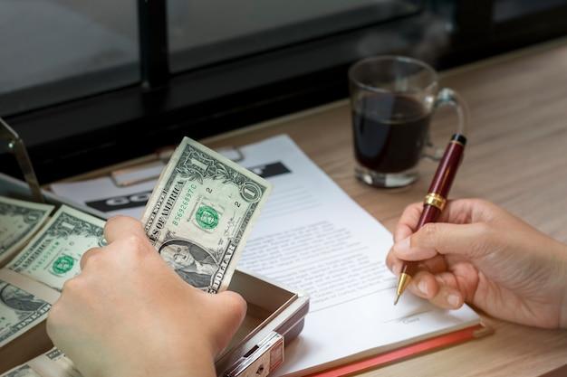 Hand van zakenmanholding pen om bedrijfsdocument en contactblad te schrijven