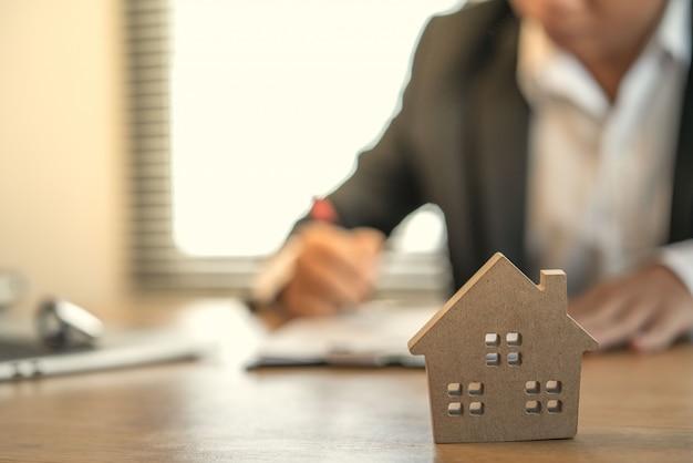Hand van zakenmensen die rente, belastingen en winst berekenen om te investeren in onroerend goed en huizen kopen