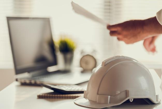 Hand van zakenmensen werkdocument over budgetwinsten en planning van bouwproject