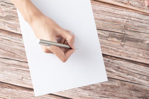 Hand van zakenvrouw schrijven op papier op kantoor