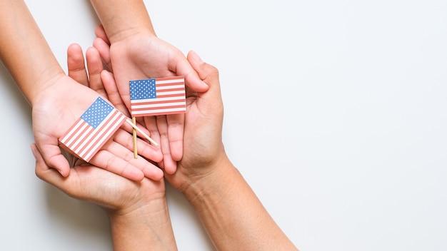 Hand vasthouden en aanraken van de nationale mini amerikaanse vlag. wereld veteraan dag concept