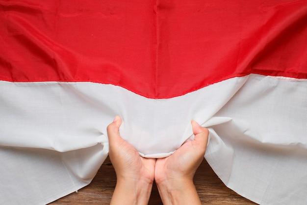 Hand vasthouden en aanraken van de nationale vlag van indonesië rood en wit, indonesië onafhankelijkheidsdag concept