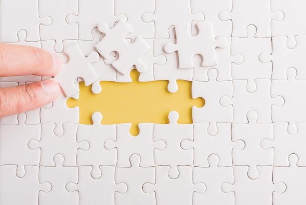 Hand vasthouden laatste stuk wit papier puzzel spel laatste stukjes op hun plaats voor het oplossen van het probleem, de volledige missie