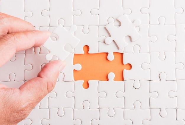 Hand-vasthouden laatste stuk wit papier puzzelspel laatste stukken op hun plaats
