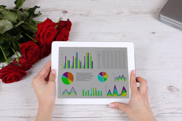 Hand vasthouden tablet en aanraken van werkruimte op tafel met rozen