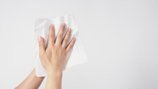 Hand veegt papieren zakdoekje op witte achtergrond.