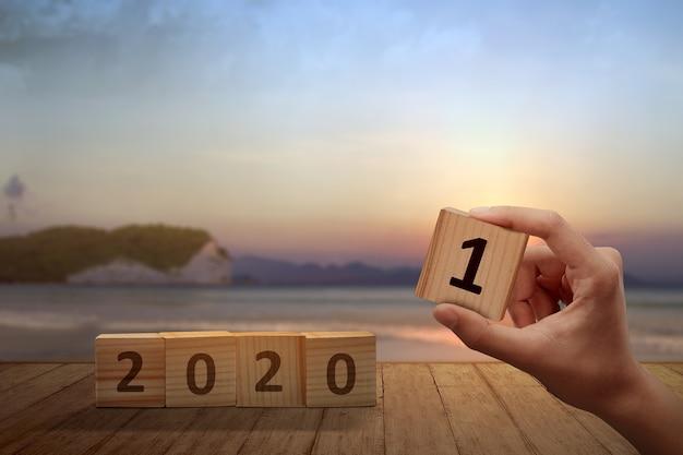 Hand verandert de houten kubus van 2020 tot 2021