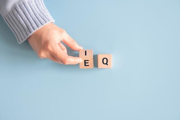 Hand verandert houten kubus de uitdrukking iq in eq