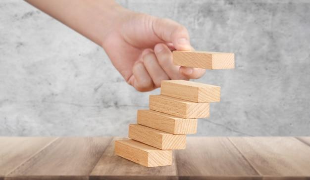 Hand vergelijken persoon opvoeren houtblok stapelen als stap trap