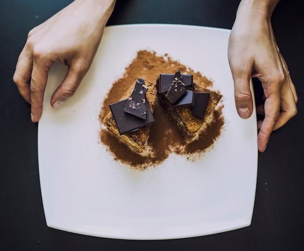 Hand versierd met mooie chocolade cake van vrouwen close-up op tafel