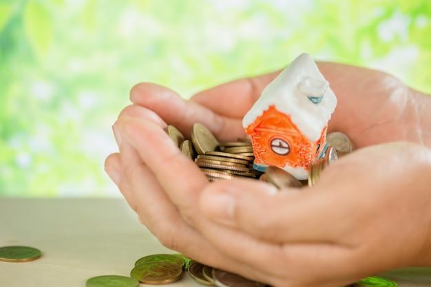 Hand verwende munten en kleine huis-model