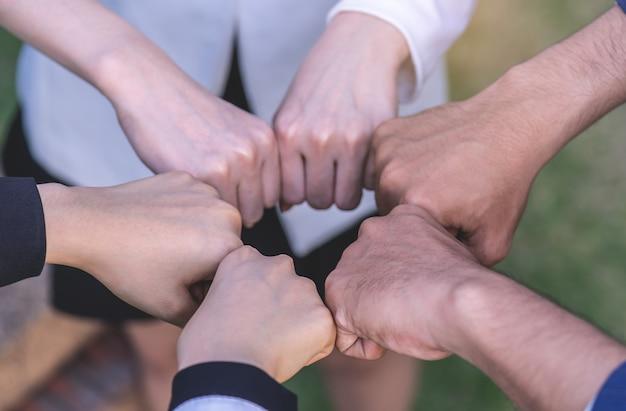 Hand vier samen in commerciële vergadering voor teamconcept