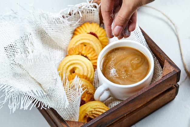 Hand voegt poeder toe aan de koffie en een bord met koekjes.