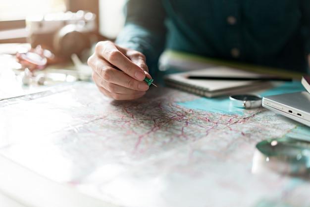 Hand voor het plannen van vakantiereizen en accessoires voor reizen
