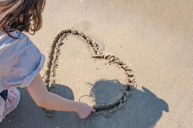 Hand vrouw harten puttend uit het zandstrand