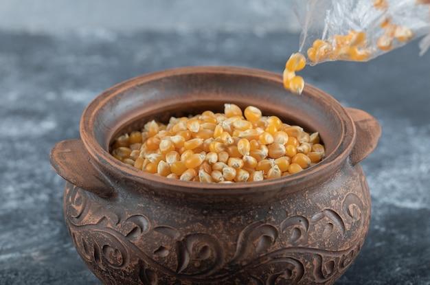 Hand vullen van een kom met ongekookte popcornzaadjes op marmer.