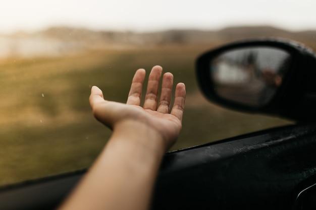 Hand wat betreft regendruppels. spiegel gezien door het glas. nat autoraam. sluit omhoog regendaling. auto uitzicht zie de spiegel. regenachtige dag.