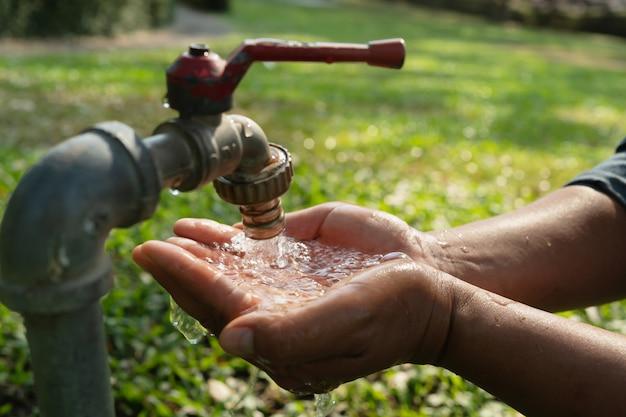 Hand water uit de kraan om te drinken.