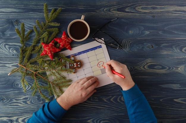 Hand wijst 25 december in een kalender omgeven door kerst ornamenten