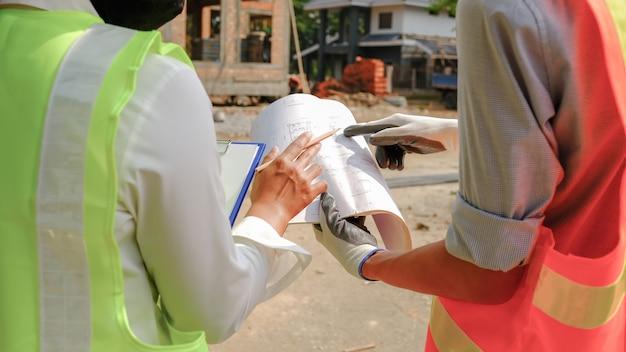 Hand wijzend huisplan, engineer aannemersteam dat werkveiligheidsindustrieproject ontmoet en ontwerp op de bouwplaats controleert.