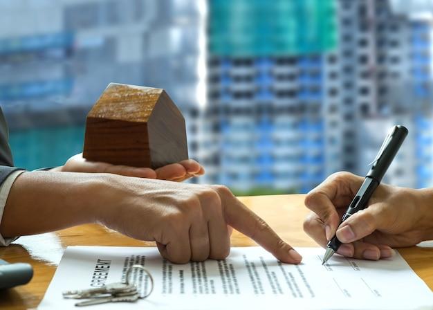 Hand wijzende klant waar contract te ondertekenen.
