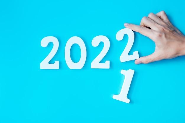 Hand wijzigen 2021 tot 2022 nummer op blauwe achtergrond. plan, financiën, resolutie, strategie, oplossing, doel, zakelijke en nieuwjaarsvakantieconcepten