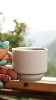 Hand witte kop warme koffie. in de ochtend, koud uitzicht op de bergen, zachte focus, wazig