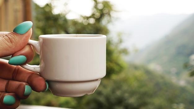 Hand witte kop warme koffie. 's morgens koud uitzicht op de bergen