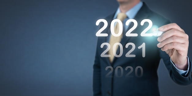 Hand zakenman 2022 nummer schrijven op virtueel scherm. zakelijke en technologische doelen stellen doelen en prestaties in 2022 nieuwjaarsresolutie, planning en startstrategieën en ideeën