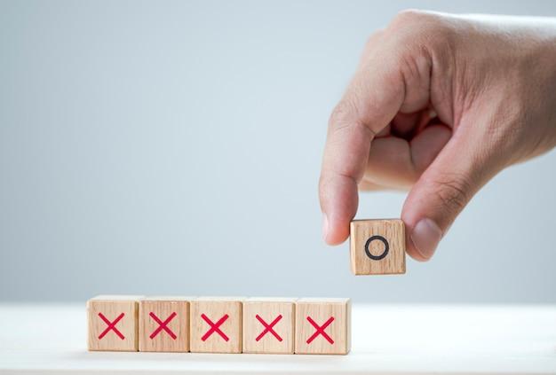 Hand zet o symbool printscherm op houten kubus en x houten kubussen