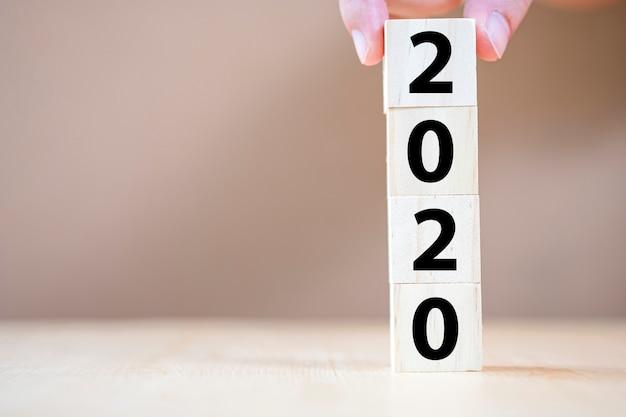 Hand zetten houten kubus voor het nieuwe jaar 2020. nieuwjaar vakantie begint.