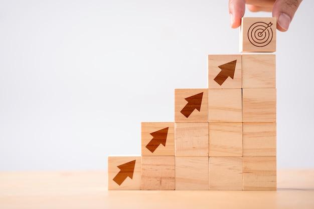 Hand zetten print scherm dart en doelbord houten kubus op pijlen. doelwit van investeringen en business concept.