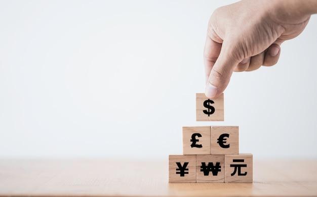 Hand zetten us dollarteken op de top van renminbi yuan yen euro en pond sterling teken.
