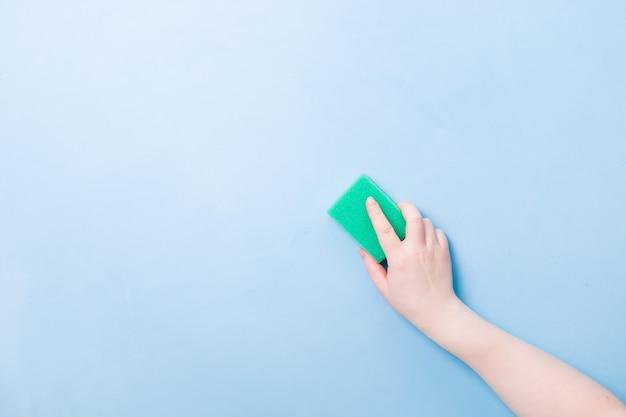 Hand zonder handschoen houdt een groene spons vast voor afwassen en schoonmaken
