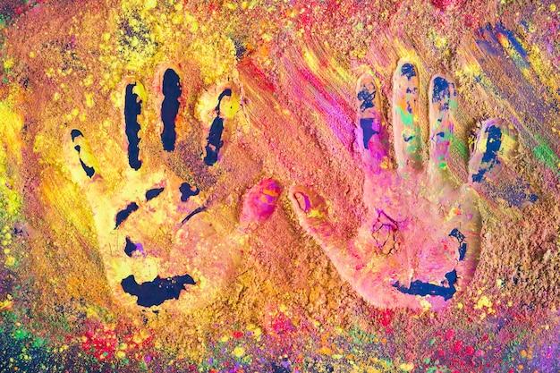Handafdrukken op kleurrijk poeder