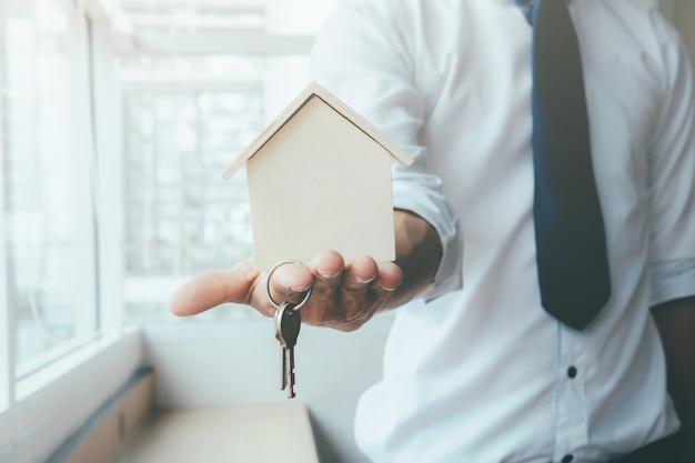 Handagent met huis in palm en sleutel op vinger.