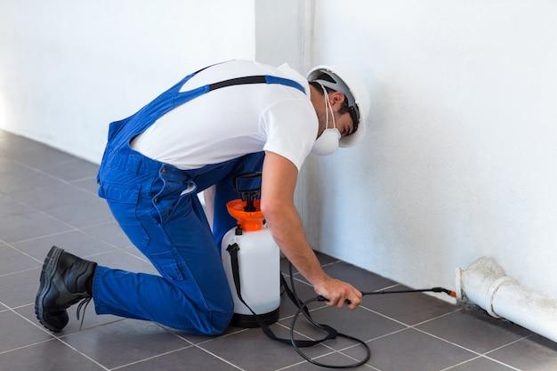 Handarbeider bespuitend insecticide op pijp