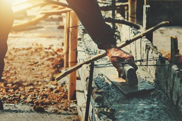 Handarbeider die beton voor mengelingscement nivelleren bij bouwwerf