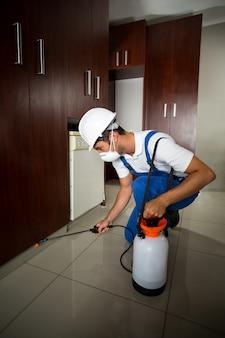 Handarbeider die insecticide onder kabinetten bespuiten