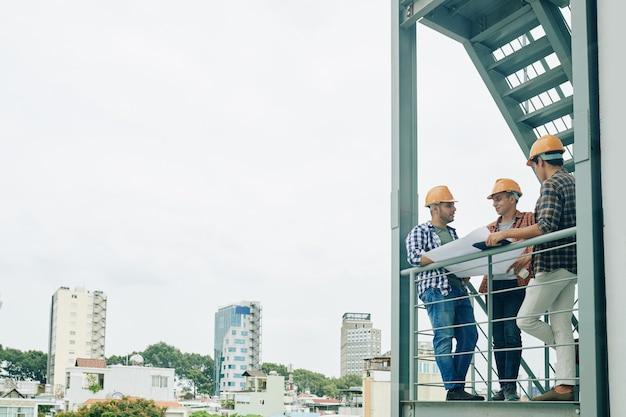 Handarbeiders met bouwplan