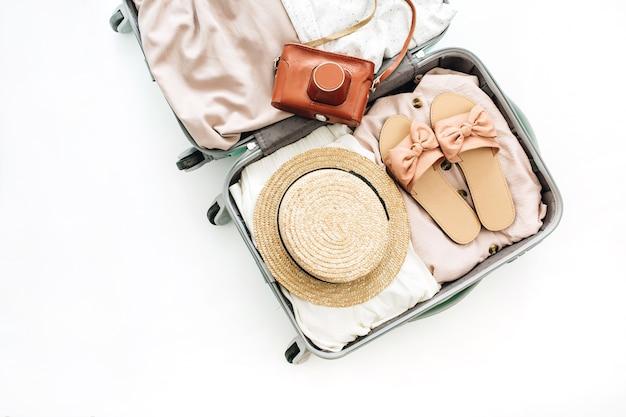 Handbagage met stijlvolle vrouwelijke kleding en retro camera op witte achtergrond. platliggend, bovenaanzicht
