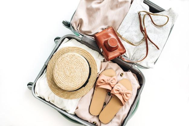 Handbagage met stijlvolle vrouwelijke kleding op witte achtergrond. platliggend, bovenaanzicht