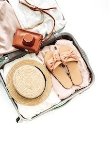 Handbagage met vrouwelijk stro, pantoffels en retro camera op witte achtergrond. platliggend, bovenaanzicht