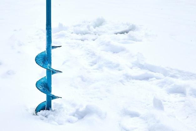Handbediende ijsvijzel gebruikt bij het ijsvissen. blauwe metalen schroef. boren. hobby's, wintervissen op besneeuwd meer