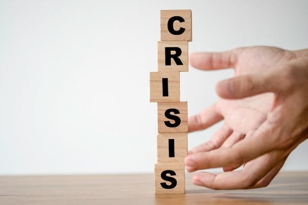 Handbescherming houten blokjes blok die crisis crisis formulering afdrukken. financieel en economisch crisisconcept.