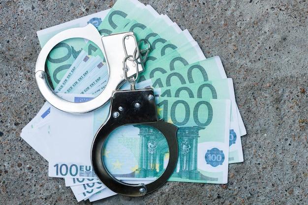 Handboeien liggen op een bundel van honderd euro. gevangenis lening concept. hoge kwaliteit foto