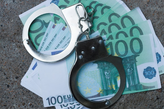 Handboeien liggen op een bundel van honderd euro. gevangenis voor schulden concept. hoge kwaliteit foto